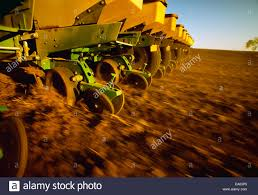 John Deere Planters by Agriculture Low Angle View Of A John Deere Planter Planting Corn