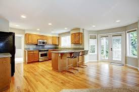 large empty open kitchen with living room with balcony doors