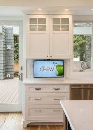 kitchen television ideas glass front ivory kitchen cabinets are mounted above ivory shaker