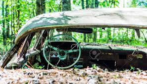 wrecked car an old wrecked car in the woods with glass broken out stock photo