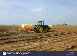 a tractor equipped with a sprayer applies a pre plant herbicide to