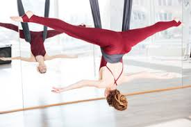 beautiful redhead young woman doing pose of aerial yoga using