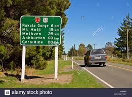 country towns suv passes signpost for canterbury high country towns new zealand