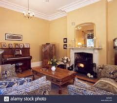 blue sofas and indonesian coffee table set around marble fireplace