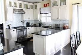 glass countertops kitchens with white cabinets and dark floors