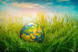 globe lies on green grass concept earth day stock photo