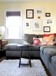 gray couch dark floors light rug light walls red and orange