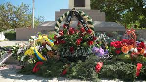 remembrance wreaths and flowers on ww ii war memorial tilt