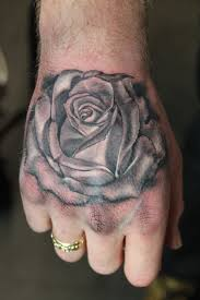grey rose and head tattoo on left hand