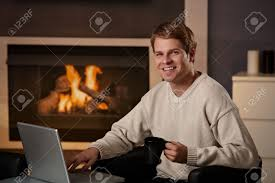 happy young man sitting in front of fireplace at home on a cold