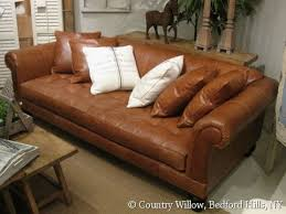 brown single cushion leather sofa with toss pillows and tufted