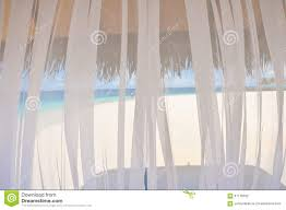 view to white tropical beach through transparent window curtain
