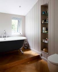 the bathroom has a raised platform for the freestanding bath and
