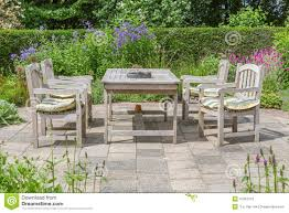 wooden table and chairs in an ornamental garden stock image