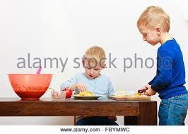 child cut apple with a kitchen knife cooking stock photo royalty