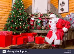 bearded santa claus sitting in a chair gift boxes fireplace and
