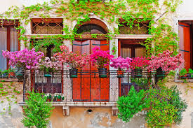italian windows with balcony decorated with fresh flowers stock