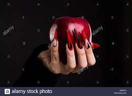 black scary halloween background hands with scary nails manicure holding red apple isolated on