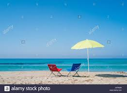 Chairs On A Beach Yellow Beach Umbrella And Two Lounge Chairs On A Beach In Sardinia