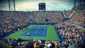 people sitting on bench watching tennis event on field during