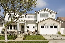 classic white and stone exterior with a barn style garage door