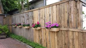 a pallet fence with flower boxes and bee hotels 3 steps