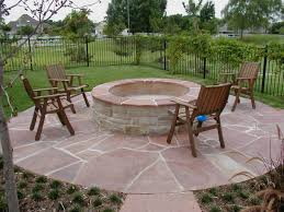 backyard landscaping ideas with concrete firepit on flagstone