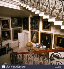 large portraits in hall of stately home with ornate banisters on