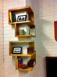 corner triangle brown wooden wall shelves with stand on white wall