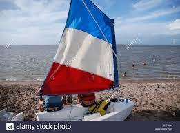 Blue Flag Yachts French Flag Sail On A Sailing Boat On The Beach Stock Photo