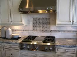 white kitchen backsplash with marble countertop between gas stove