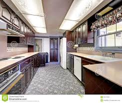 old wood narrow kitchen with carpet and curtains stock images