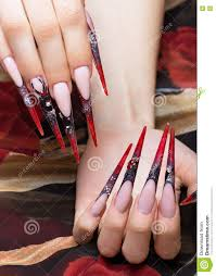 long beautiful manicure on the fingers in black and red colors