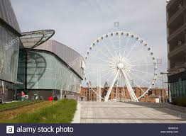 ferris wheel echo arena and albert dock in liverpool uk stock