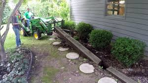 john deere 1025r rips out railroad ties boomerangs bushes and