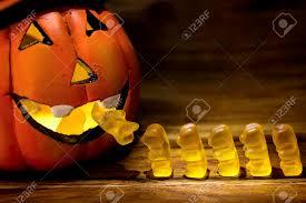 halloween pumpkin eating a row of gummy bear for trick or treat