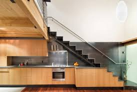 Under Stairs Pantry by Loft Modern Bright Apartment With Wood Kitchen And Staircase Stock