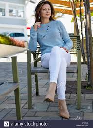 elegant mature woman portrait of elegant mature woman sitting on patio chair stock photo