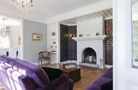 warm living room with purple sofa and fireplace mantels for the