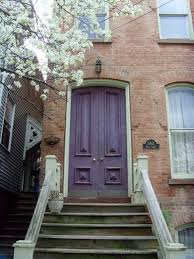 purple door with clay coloured brick house may be the color i am