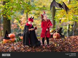 two funny kids wearing devil and vampire costume with red horns
