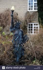 a statue of liberty garden ornament in an overgrown garden
