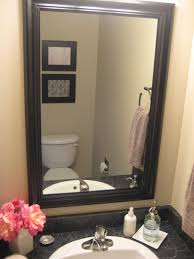 gray wall paint mirror with black wooden frame toilet paper holder