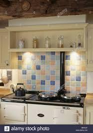 cream shelf and pastel ceramic tiled splash back above white aga