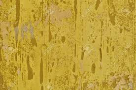 peeling paint yellow wall and pieces of torn wallpaper background