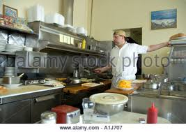 short order cook preparing food on a grill in a small restaurant