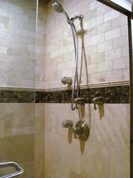 custom travertine shower with dark emperador marble trim multi