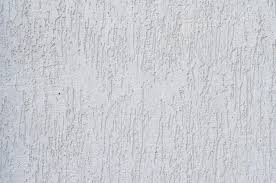 Textured Paint For Exterior Concrete Walls - background of a white stucco coated and painted exterior rough