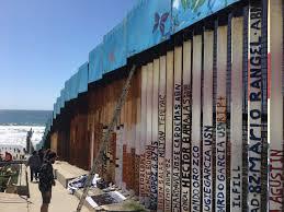 tijuana artist works to paint the longest mural on the border wall border wall art on the tijuana side 2017
