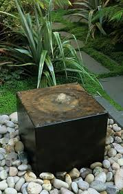 garden with river rocks and square stone fountain wonderful